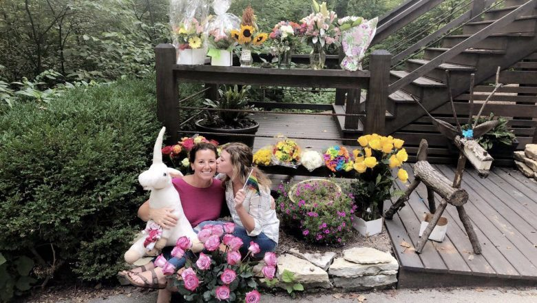 A teacher surrounded by flowers and family.