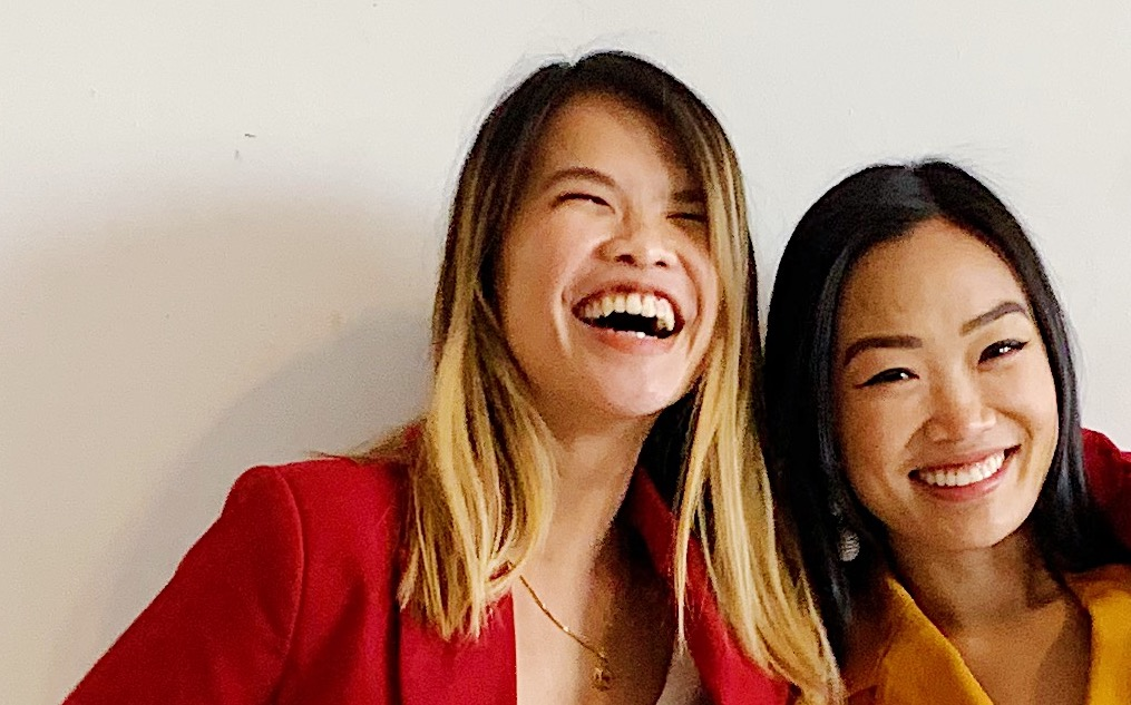 Two Women leaning into each other and laughing, in brightly colored suits