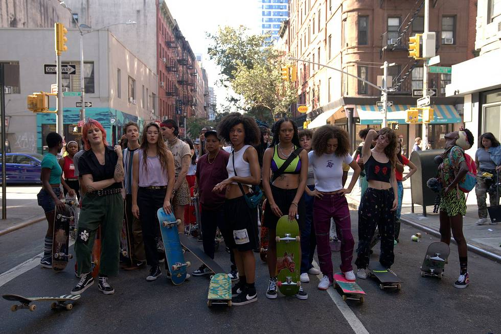 A crowd of women from HBO's Betty, a show about skater girls navigating the male-dominated NYC skate scene, stand together on a street facing the camera with their skateboards.