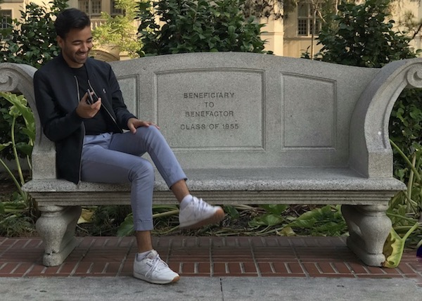 Juan Mireles-Palomar, a gay 21-year-old recipient of DACA (also known as Deferred Action for Childhood Arrivals), sits on a bench smiling as he attempts to cross his legs.