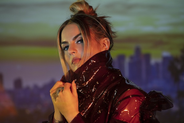 R&B singer-songwriter JoJo, also known as Joanna Levesque, looks at the camera confidently while popping the collar of her jacket.