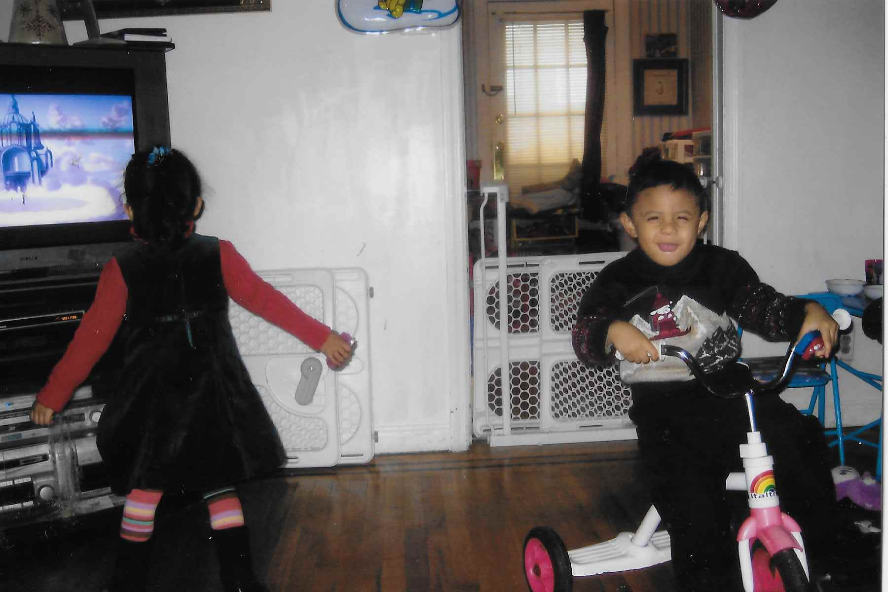 A little girl stands in front of a TV so her back is facing the camera. Her twin brother is looking at the camera with a scrunched face while riding a tricyle inside their family's living room.