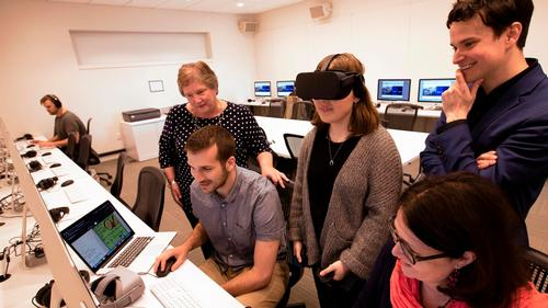Kyra Richardson '21 uses an Oculus Rift. Along with Andrew Groll '19 (seated), she designed a VR environment and 3D objects. Members of the library's Digital Learning and Research team look on.