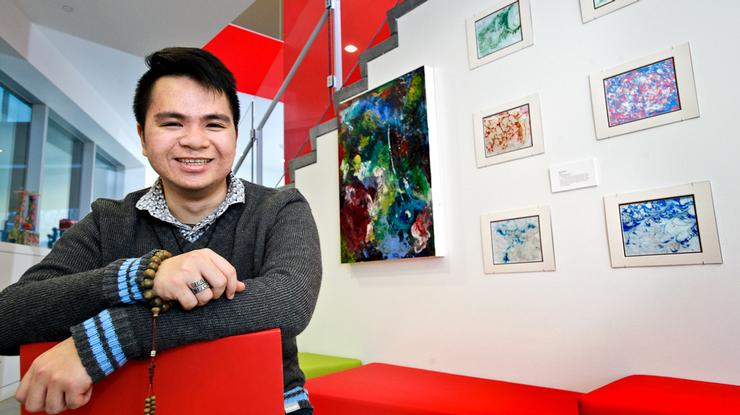 Minh Nguyen '17 is seated in front of a display of his art in the Kennedy Center for Theatre and the Studio Arts.