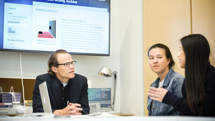 Doran Larson, the Walcott-Bartlett Chair of Ethics and Christian Evidences, talks with Shirley Luo '17, right, and Clara Cho '20 in the The Digital Humanities Initiative lab in Christian A. Johnson Hall.