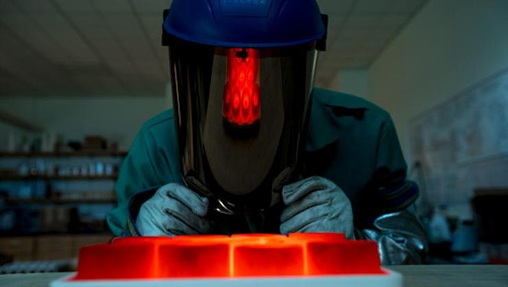 Behind the protective gear is Robert Welch '20, who examines a tray of cooling beads for rejects after removing them from the muffle furnace.