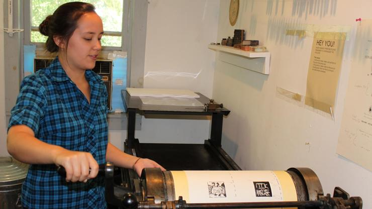Cat Boyd '12 works the press at the Women's Studio Workshop.