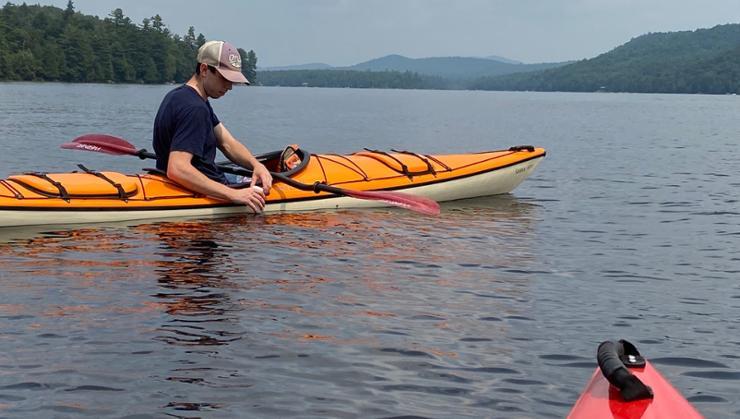 Caleb Phelan '22 collects water samples in the Adirondacks.