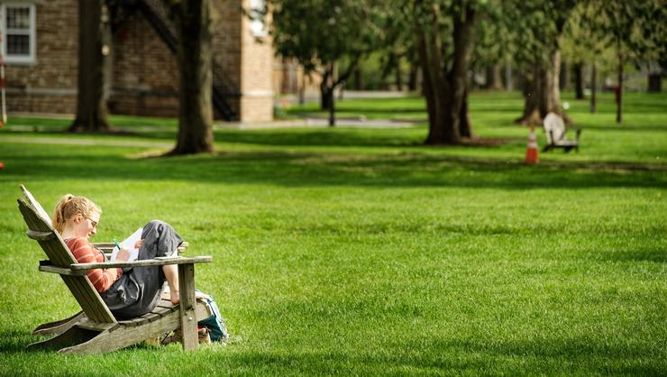 A student enjoys the quiet summer campus.