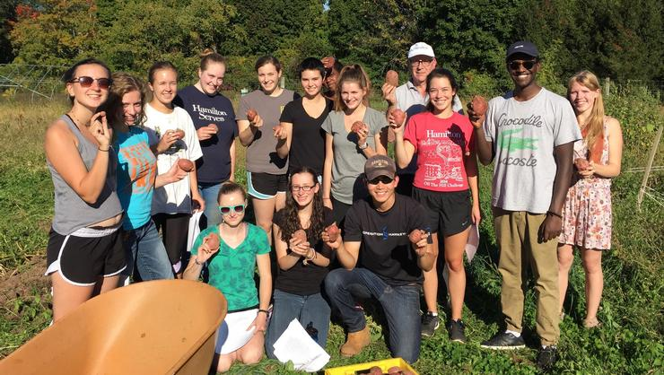 Students in College 236 show off their potato harvest.