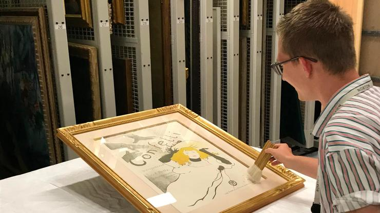 Louis Dzialo '19 works on a Toulouse-Lautrec poster in the storage area at the Norton Museum.
