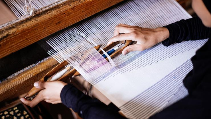 An Arabesque worker learns to use a silk weaving loom.