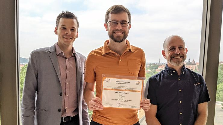 Professor Tom Helmuth (center) and his co-authors earned a Best Paper Award for