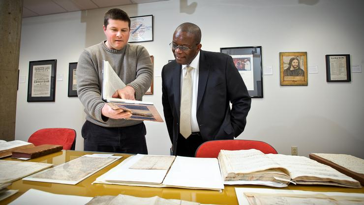 Director and Curator of Special Collections and Archives Christian Goodwillie shows Ambassador Everson Hull some pieces from the College's Beinecke Lesser Antilles Collection.