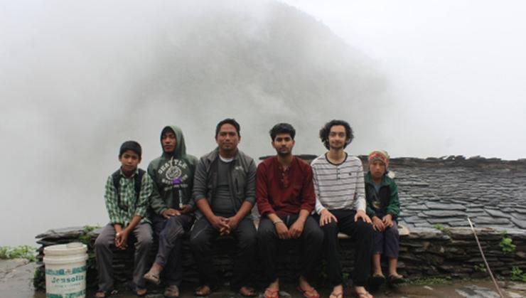 Ishan Mainali '21 with Sagar, their host, and village kids.