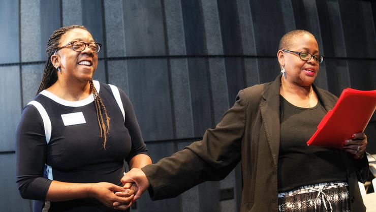 Phyllis Breland, Director of Opportunity Programs, (right) reads her testimonial honoring Josie Collier '97, P'14 as Collier receives the