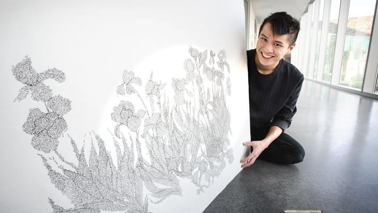 Smallen grant recipient Matt Tom '20 with one of his rice drawings in Kennedy Arts Center.