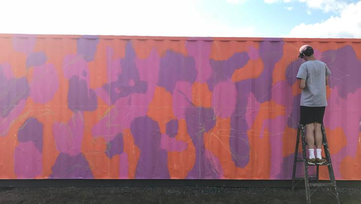 Visiting Assistant Professor of Art Max Ferro paints a mural on a shipping container in Utica.