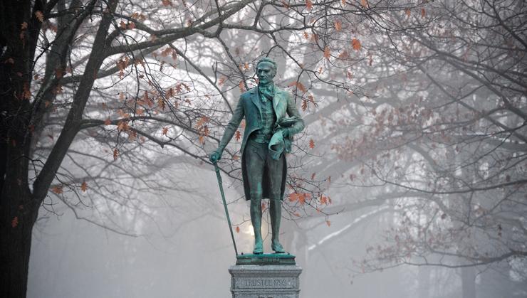 The Alexander Hamilton statue overlooks a foggy campus in winter at Hamilton.