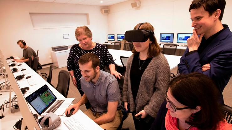 Students use an Oculus Rift while designing a VR environment and 3D objects while members of the library's Digital Learning and Research team look on