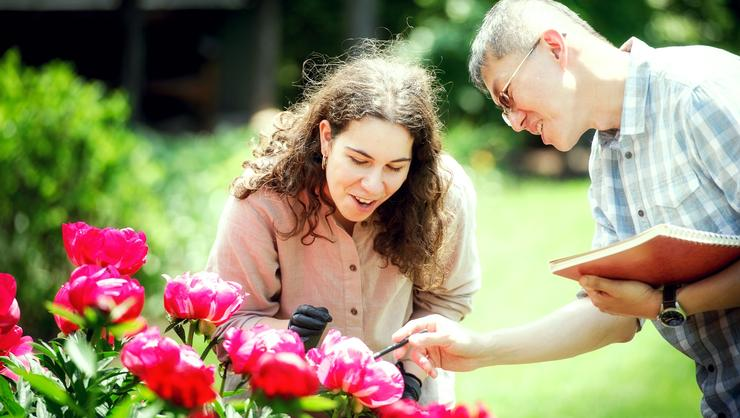Tara Cicic '18 and Associate Professor of Biology Wei-Jen Chang examine peonies in Grant Garden.