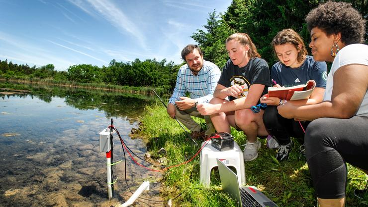 From left, Professor Aaron Strong chats with Pauline Santry '21, Lucille Kline '22, and Emely Chacon '22 as they use equipment to measure the amount of methane gas being released from the Hamilton Reservoir.