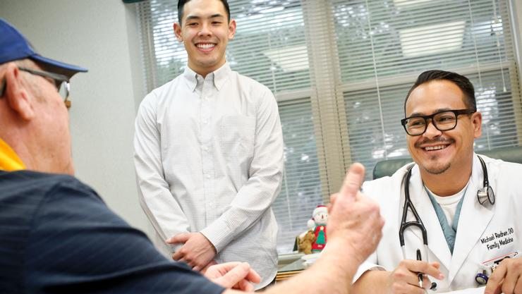 Hamilton student Aaron Oh '17, center, observes as St. Elizabeth Family Medicine Resident Michael Redner, DO, has a follow-up visit with Robert Williams of Beaver Falls at Central New York Cardiology.