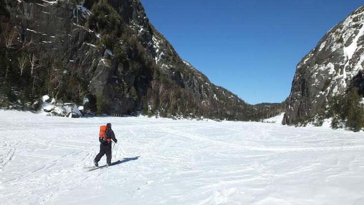 Trip leader and instructor Kevin Roback '17 skis across a frozen lake at the top of Avalanche Pass.