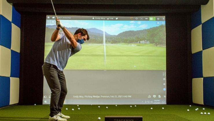 Men's golf captain Thomas Graham '21 practices his golf swing using the new golf simulator.
