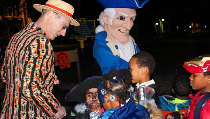 President David Wippman and Alex the Mascot hand out candy to trick-or-treaters.