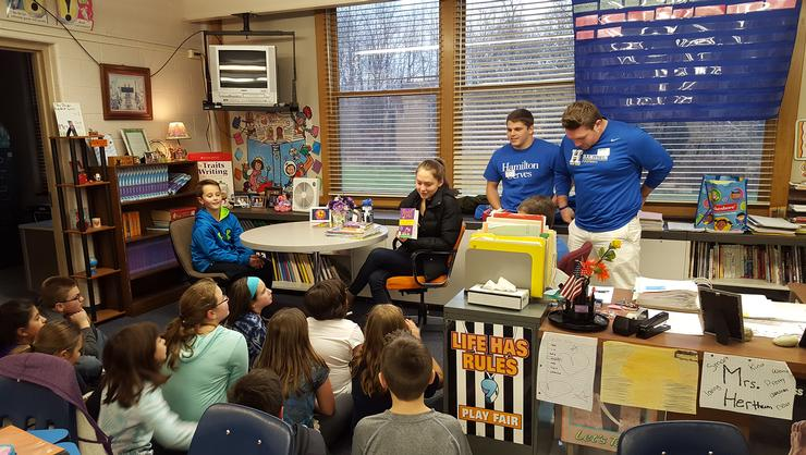 Student athletes Abby Uehling '18 (cross country), Kory Fogarty '19 (football) and Zachary Altneu '18 (football) read to children in a Whitesboro elementary school classroom.