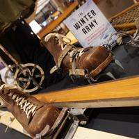 Skis and boots worn by soldiers in the 10th Mountain Division, with a copy of The Winter Army.