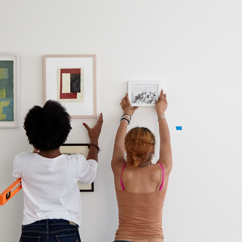 students hang works in the critique space