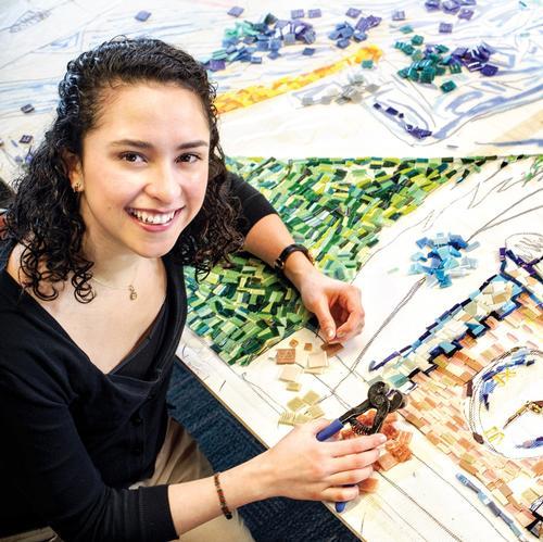 Irina Rojas works on the community mosaic