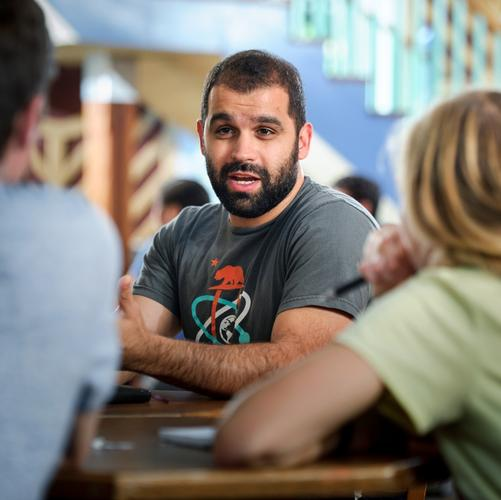 Assistant Professor of Economics Mo Alloush speaks with students