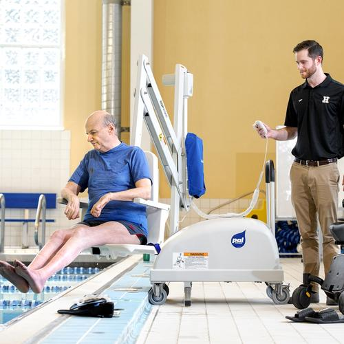 Swim Coach John Geissinger operates the aquatic pool lift for Henry Kaufman while Associate Dean Allen Harrison looks on.