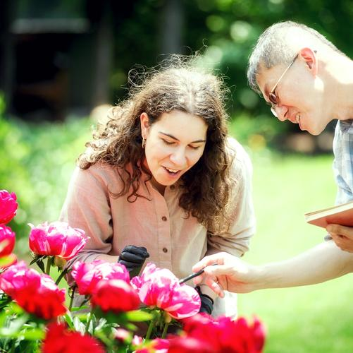 Tara Cicic '18 and Wei-Jen Chang with peonies, grant garden