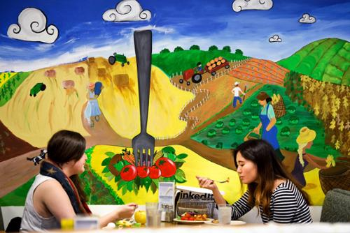 Students eating in McEwen in front of mural