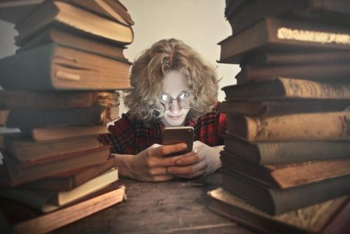 student browsing phone with books