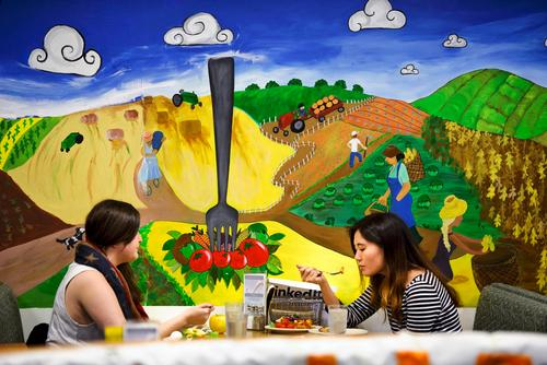 Students eating in McEwen in front of mural