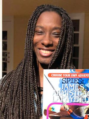 Kyandreia Jones '19 shows the cover of her new book.