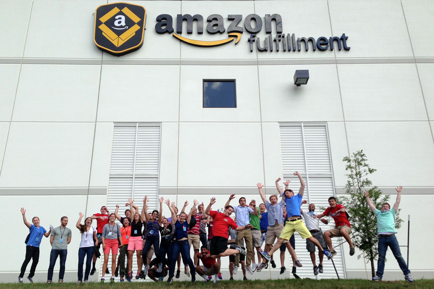 Amazon interns jumping in front of a fulfillment center