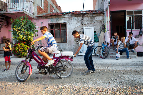 Özenç, 11 ans sur sa mobylette et son frère poussant pour la faire démarrer pendnt que sa mère et son père sont assis sur le pas de la porte, quartier gypsy de Canakkale, Turquie / Özenç, 11 years old on his motorcycle and his brother pushing to launch it and mother and father sitting on the doorstep, Canakkale, Turkey