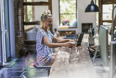 Woman sitting in kitchen, using laptop