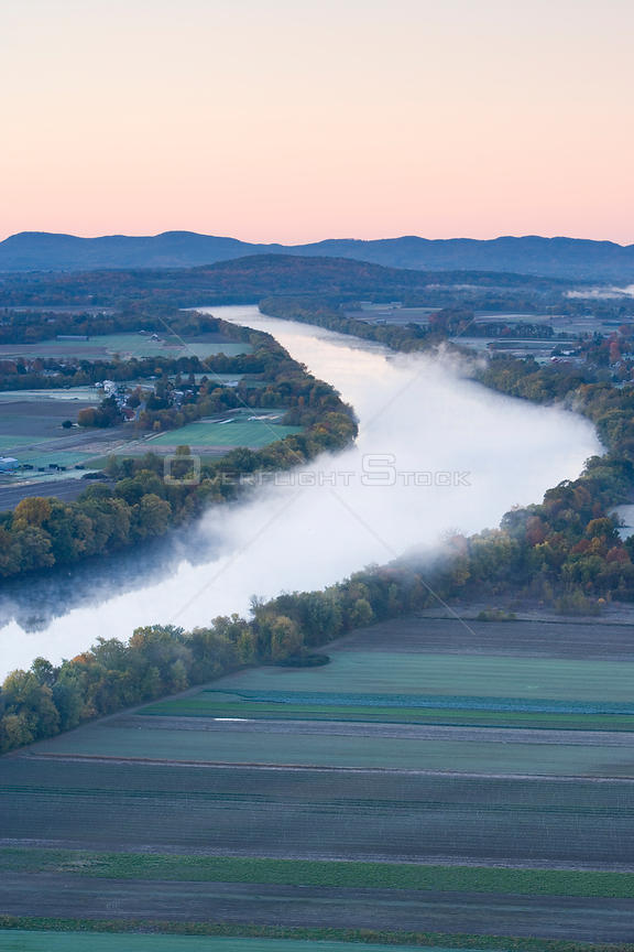 Aerial view of mist rising from the Connecticut River at dawn as seen from South Sugarloaf Mountain in the Sugarloaf Mountain State Reservation, Deerfield, Massachusetts, USA, October 2006