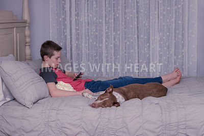 Boy and dog reclining on bed