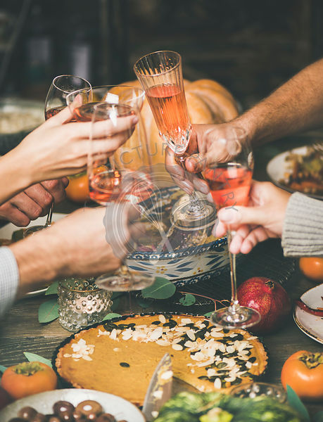 Friends clinking glasses at festive New Year table with snacks