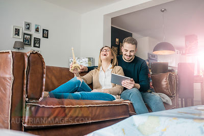 Happy couple sitting on couch at home with tablet and Eiffel tower model