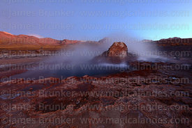 Boiling spring and geyserite mineral deposits at El Tatio geyser field at twilight, Region II, Chile
