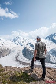 Hiker looking at Monte Rosa glacier and peaks, Gornergrat, Zermatt, Switzerland
